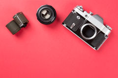 Old film camera with lens and film on red background. Top view. Royalty Free Stock Image