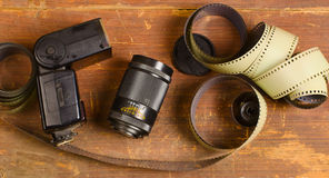 Old film for the camera, a lens and flashlight Royalty Free Stock Photo