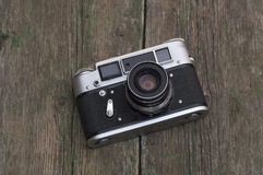 The old film camera lies on a wooden table Stock Images
