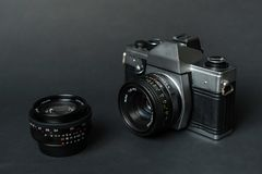 Old film camera and manual lens, black background. Old film camera and manual lens, black background Royalty Free Stock Images