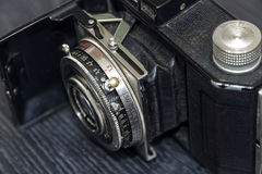 Old film camera in the open state on a dark background. The product of the early 20th century. Old-fashioned film camera on a dark background stock images