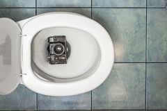 The old film camera recessed in the toilet royalty free stock photography