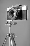 Old film camera and retro steel tripod Stock Image