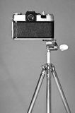Old film camera and retro steel tripod Royalty Free Stock Image