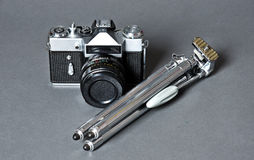 Old film camera and retro steel tripod Stock Photography