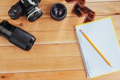 The old film camera and roll film and notebook with pencil on a wooden background.  Royalty Free Stock Photos