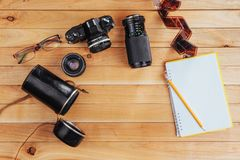 The old film camera and roll film and notebook with pencil on a wooden background.  Stock Images