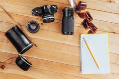 The old film camera and roll film and notebook with pencil on a wooden background.  Royalty Free Stock Photography