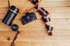 Old film camera and a roll of on wood. Old film camera and a roll of film on wood Royalty Free Stock Image