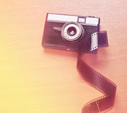 Old film camera and some film. Old film camera with lens, a  roll of film lying on a wooden surface Royalty Free Stock Photo