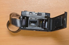 Old film camera and some film. Old film camera with lens, a  roll of film lying on a wooden surface Stock Image