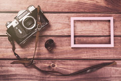 Old film camera with strap, photo frame and film on wooden background. Vintage toned and top view Royalty Free Stock Photos