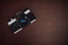 Old film camera on a wooden table Royalty Free Stock Photo