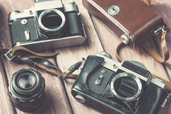 Old film cameras with lens and case on wooden background. Vintage toned and selective focus Stock Photos