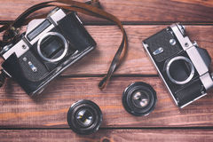 Old film cameras with lenses and strap on wooden background. Vintage toned and top view Stock Image