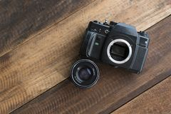 Old film DSLR camera with lens on a wooden table. Photography concept Royalty Free Stock Photo