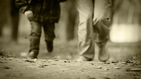 Old film effect: Father and son Jogging in Autumnal park stock footage