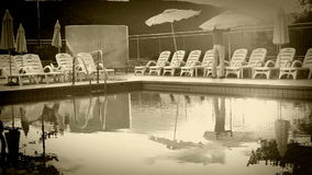 Old film effect: Luxury resort pool in the evening time - worker folds down the umbrellas stock footage