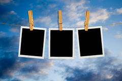 Old Film Frame over Sky. Old photo film blanks hanging on a rope held by clothespins over blue sky Stock Images