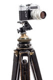 Old film photocamera on wooden tripod. Stock Images