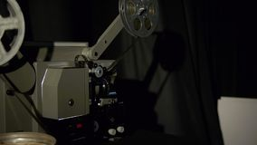 Old film projector playing in the night. Close-up of a reel with a film. Operation of the film projector mechanism stock video footage