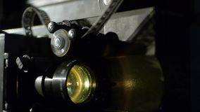 Old film projector playing in the night. Close-up of a reel with a film. Operation of the film projector mechanism stock footage