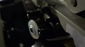 Old film projector playing in the night. Close-up of a reel with a film. Operation of the film projector mechanism stock video