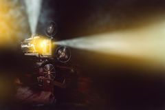 Old film projector with smoke in dark room royalty free stock image