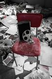 Old film reel for a projector on a red chair. In a room strewn with heaps of debris, torn papers and filth in a derelict building Royalty Free Stock Image