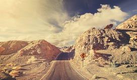 Old film retro stylized rocky desert road. Stock Photos