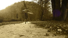 Old film styled footage: merry little boy jumping by the park with an umbrella stock video