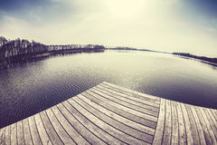 Old film stylized fisheye lens image of a wooden pier at sunset. Royalty Free Stock Photos