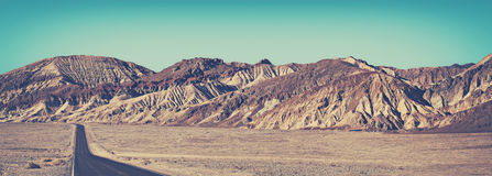 Old film stylized panoramic picture of desert road. Royalty Free Stock Image