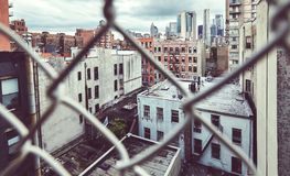 Downtown New York seen through the chain link fence. Old film stylized picture of downtown New York seen through the chain link fence Royalty Free Stock Image