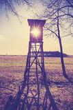 Old film vintage stylized hunting pulpit against sun. Royalty Free Stock Images