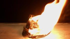 Old filmstrip burning. Against dark background closeup stock footage
