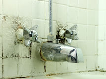 Old Filthy Faucet. An old abandoned filthy antique faucet with cracking and rusted walls Stock Photography