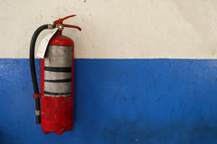 Old fire extinguisher tank on grunge blue wall Stock Images