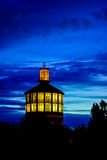 Old fire tower lightened in the dusk. Iluminated old architecture fire tower over the blue sky Stock Images
