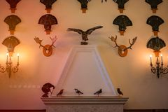 Old fireplace in castle room with trophies. Stuffed birds and animal`s horns on wall with lamps royalty free stock image