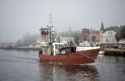Old fishboat entering Ustka harbor in Poland Stock Images