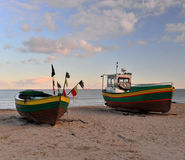 Old fishboats on the beach. Two small fishboats, one wooden and one made of fiberglass, on the beach in Sopot, Northern Poland, near the Bay of Gdansk, the Stock Images