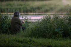 Old fisher with rod near the water stock photography