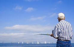 Old fisherman. Fishes and observes a yachts regatta Stock Photo