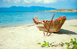 Old fisherman boat with anchor on the beach Royalty Free Stock Image