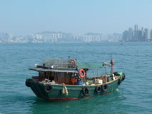 Old fisherman boat with tall building back ground. Old fisherman boat in the sea with tall building background in Hongkong stock photo