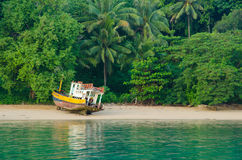 Old fisherman boat on the tropical palm beach, Thailand Stock Photo