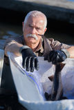 Old fisherman catching fish. Old fisherman catching a fish Stock Images
