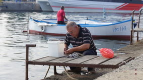 The old fisherman cut up the freshly caught fish stock footage