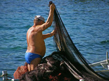 Old fisherman and fish nets Stock Images